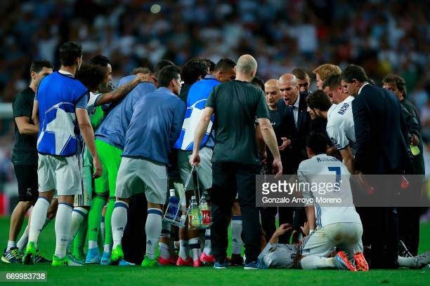 Head coach Zinedine Zidane of Real Madrid CF speaks to his team during the break of the extra time given after the UEFA Champions League Quarter...