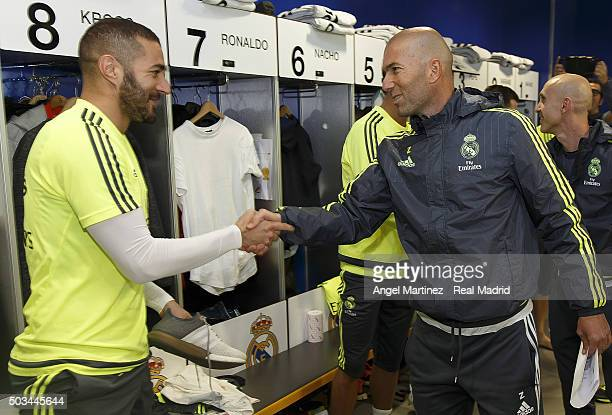 Head coach Zinedine Zidane of Real Madrid greets Karim Benzema before a training session at Estadio Alfredo Di Stefano on January 5 2016 in Madrid...