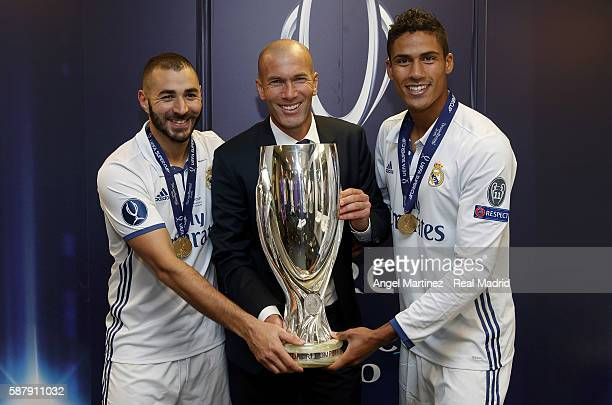 Head coach Zinedine Zidane of Real Madrid poses with Karim Benzema and Raphael Varane after the UEFA Super Cup match between Real Madrid and Sevilla...