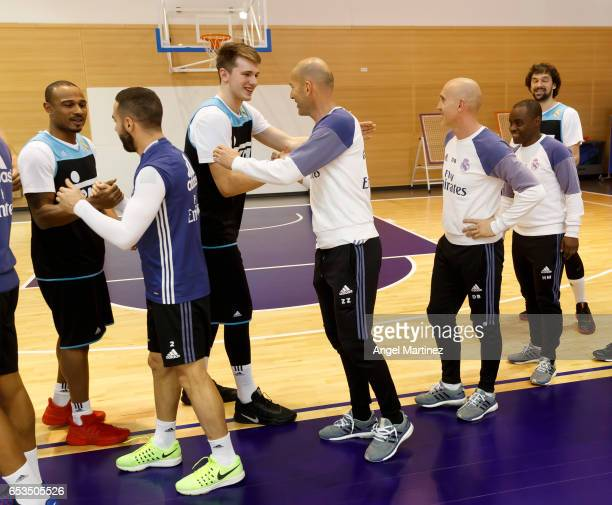 Head coach Zinedine Zidane of Real Madrid shakes hands with basketball player Luka Doncic during a training session at Ciudad Real Madrid basketball...