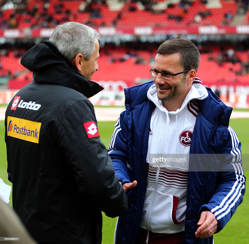 Head coaches Lucien Favre (L) of Moenchengladbach and Michael Wiesinger of Nuernberg shake hands prior to the Bundesliga match between 1. FC Nuernberg and VfL Borussia Moenchengladbach at Easy Credit Stadium on February 3, 2013 in Nuremberg, Germany.