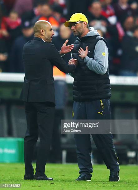 Head coaches Pep Guardiola of Muenchen and Juergen Klopp of Dortmund discuss during the DFB Cup Semi Final match between FC Bayern Muenchen and...