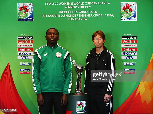 Head coaches Peter Dedevbo of Nigeria and Maren Meinert of Germany pose with the trophy during the FIFA U20 Women's World Cup Canada 2014 Press...