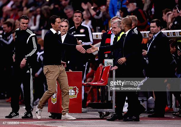 Head coaches Roger Schmidt of Bayer Leverkusen and Josep Guardiola of FC Bayern Muenchen shake hands after the Bundesliga match between Bayer 04...