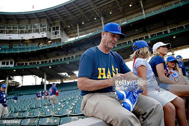 Head football coach Jim Harbaugh of the University of Michigan autographs a pair of blue cleats before the game between the Chicago White Sox and the...