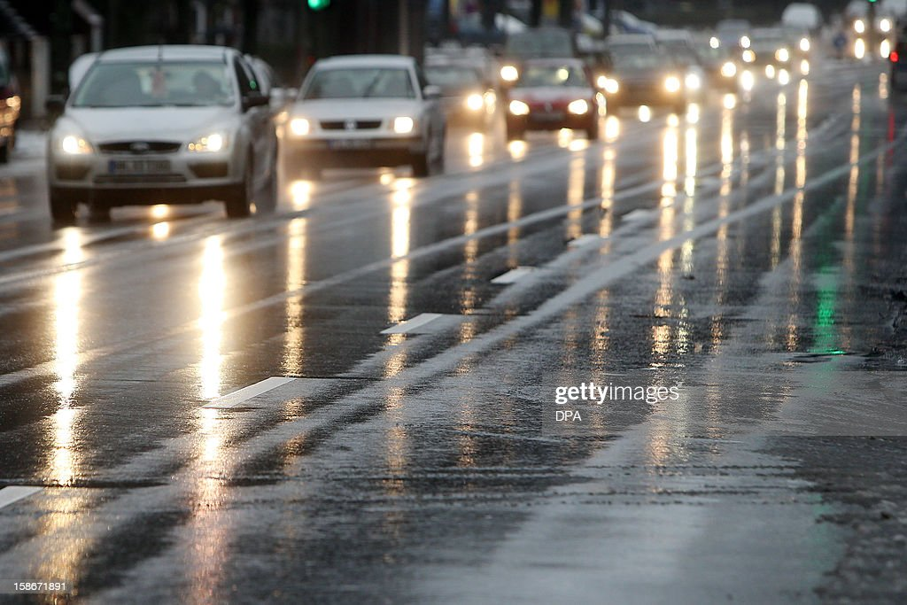 Head lamps of cars driving in Hamburg, northern Germany, reflect in the icy road on December 23, 2012. Freezing rain and snowfall disturbed traffic on many roads across the country. OUT