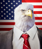 Head of an eagle on a businessman's body in front of  Stars and Stripes flag