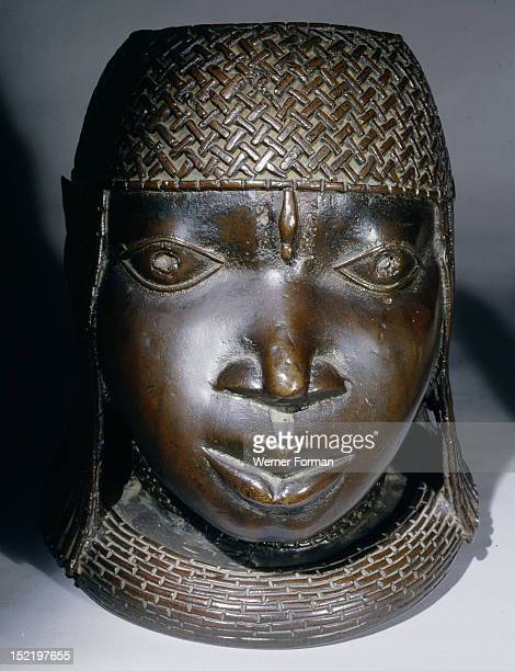 A head of an Oba from an ancestral shrine The head has a low coral collar and a beaded cap Nigeria Benin Benin
