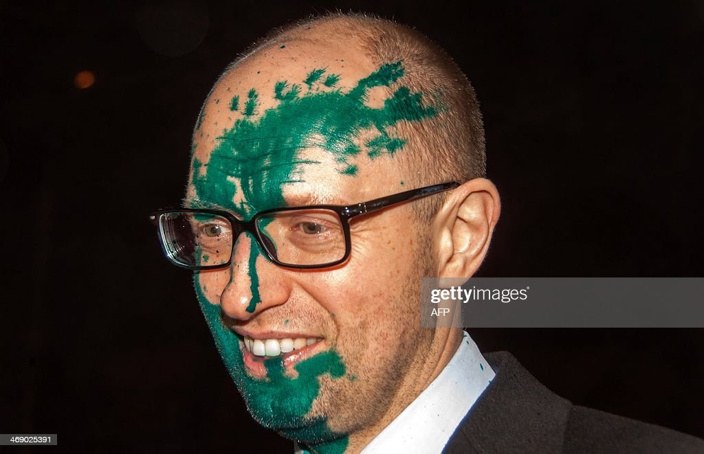 Head of Batkivschyna party Aseniy Yatsenyuk smiles as he speaks to journalists after he was attacked and doused with medical brilliant green by two unknown persons after he left the Central Clinical Hospital in Kharkiv on February 12, 2014. Yatsenyuk left the hospital after a meeting with jailed former Prime Minister Yulia Tymoshenko..