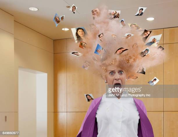 Head of businesswoman exploding with images of faces