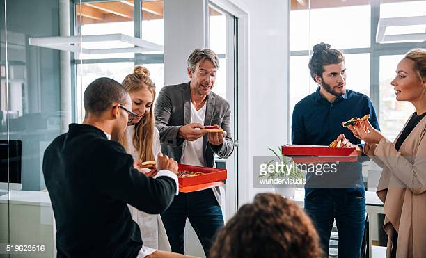 Head of department enjoying pizza with other work colleagues.