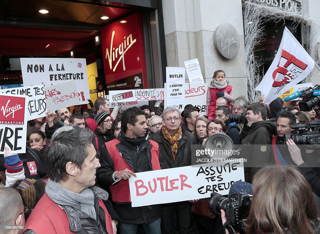 Head of French communist party Pierre Laurent (C) and French far-left Parti de Gauche (PG) vice-president Martine Billard (R) demonstrate with Virgin Megastore employees against planned job cuts at the entrance of the store on the Champs-Elysees avenue on January 9, 2013 in Paris. Virgin's Megastore music and book unit, which is known in France as a 'culture' retailer, said it will file for insolvency on January 9, 2013, and is the latest to leave the Champs as clothing chains, luxury goods shops and automobile showrooms take over. Originally started by Richard Branson, the British billionaire and chairman of the Virgin Group, the Virgin Megastores were bought by the French Lagardere group in 2001. AFP PHOTO/JACQUES DEMARTHON