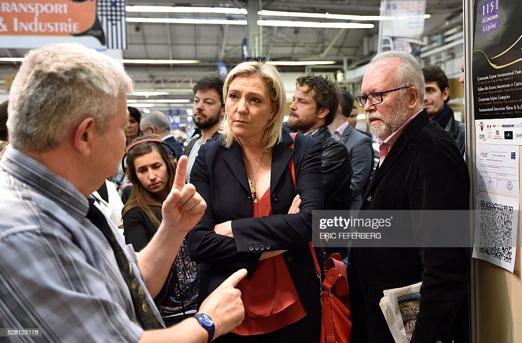 Head of French far-right party Front National (FN) Marine Le Pen (C) and FN local regional counsellor Wallerand de Saint-Just (R) visit a stand of the 'Concours Lepine' (Lepine contest) at Paris' fair, on May 4, 2016 in Paris. The Lepine contest, a competition for inventors in the world, was launched in 1901 by Louis Lepine, the city's police chief and has chalked up some notable successes, such as the world's first artificial heart in 1937. / AFP / ERIC