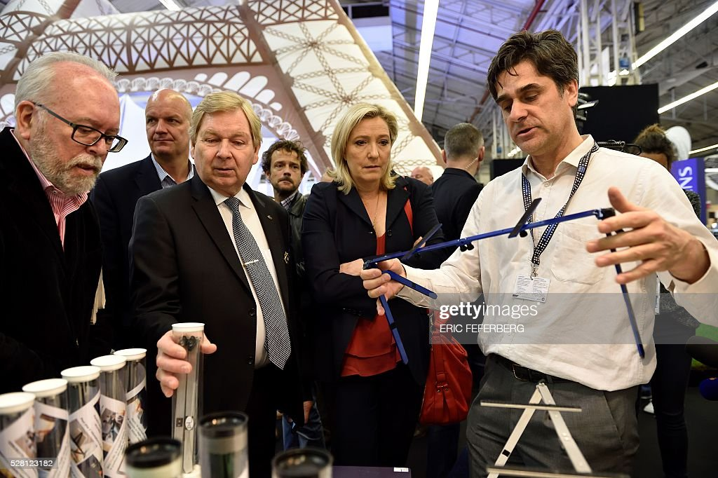 Head of French far-right party Front National (FN) Marine Le Pen (C) and FN local regional counsellor Wallerand de Saint-Just (L) visit a stand of the 'Concours Lepine' (Lepine contest) at Paris' fair, on May 4, 2016 in Paris. The Lepine contest, a competition for inventors in the world, was launched in 1901 by Louis Lepine, the city's police chief and has chalked up some notable successes, such as the world's first artificial heart in 1937. / AFP / ERIC