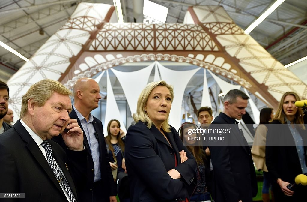 Head of French far-right party Front National (FN) Marine Le Pen (C) visits a stand of the 'Concours Lepine' (Lepine contest) at Paris' fair, on May 4, 2016 in Paris. The Lepine contest, a competition for inventors in the world, was launched in 1901 by Louis Lepine, the city's police chief and has chalked up some notable successes, such as the world's first artificial heart in 1937. / AFP / ERIC
