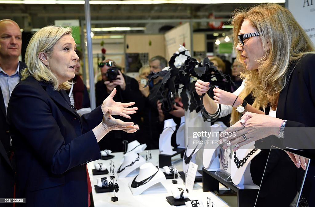 Head of French far-right party Front National (FN) Marine Le Pen (L) visits a stand of the 'Concours Lepine' (Lepine contest) at Paris' fair, on May 4, 2016 in Paris. The Lepine contest, a competition for inventors in the world, was launched in 1901 by Louis Lepine, the city's police chief and has chalked up some notable successes, such as the world's first artificial heart in 1937. / AFP / ERIC