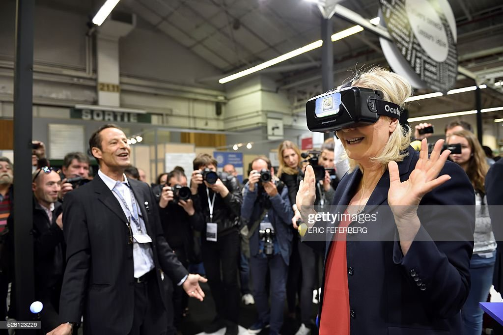 Head of French far-right party Front National (FN) Marine Le Pen (C) wears a virtual reality mask as she visits a stand of the 'Concours Lepine' (Lepine contest) at Paris' fair, on May 4, 2016 in Paris. The Lepine contest, a competition for inventors in the world, was launched in 1901 by Louis Lepine, the city's police chief and has chalked up some notable successes, such as the world's first artificial heart in 1937. / AFP / Eric FEFERBERG