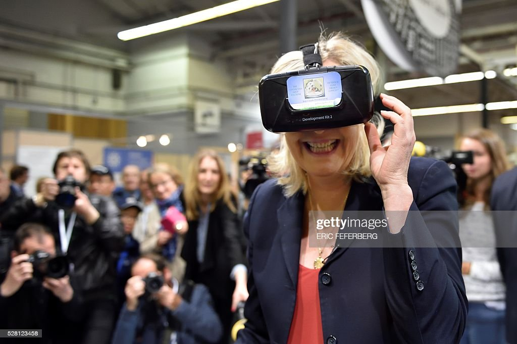 Head of French far-right party Front National (FN) Marine Le Pen (C) wears a virtual reality mask as she visits a stand of the 'Concours Lepine' (Lepine contest) at Paris' fair, on May 4, 2016 in Paris. The Lepine contest, a competition for inventors in the world, was launched in 1901 by Louis Lepine, the city's police chief and has chalked up some notable successes, such as the world's first artificial heart in 1937. / AFP / ERIC