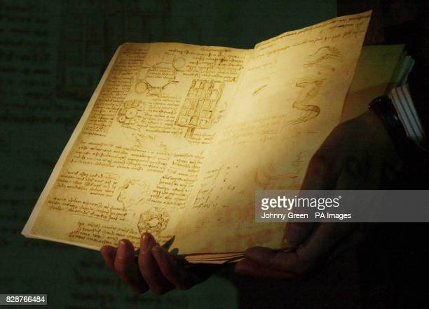 Head of Manuscripts at the British Library Christopher Wright holds part of a rare notebook belonging to Leonardo da Vinci while a digital version of...
