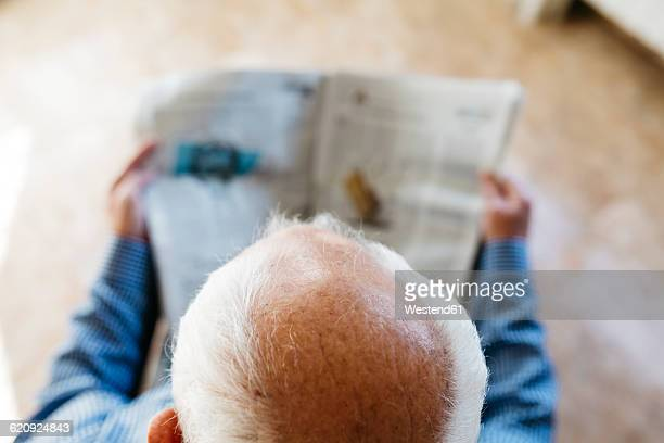Head of senior man reading newspaper at home, top view
