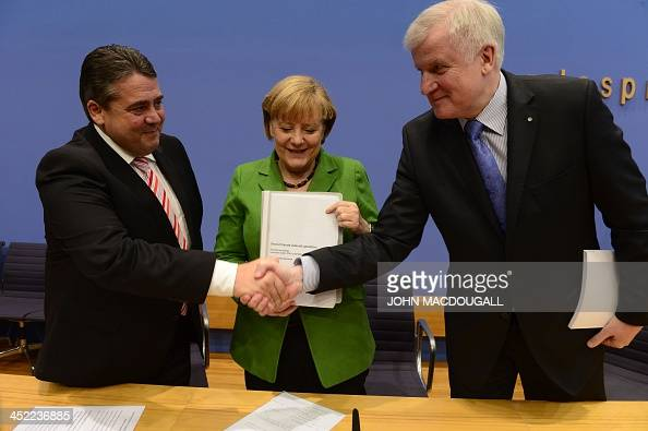 Head of Social Democratic Party Sigmar Gabriel and leader of CDU Bavarian allies Christian Social Union Horst Seehofer shake hands as German...