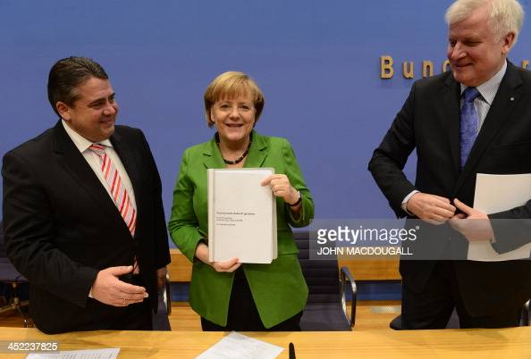 Head of Social Democratic Party Sigmar Gabriel and leader of CDU Bavarian allies Christian Social Union Horst Seehofer stand by as German Chancellor...