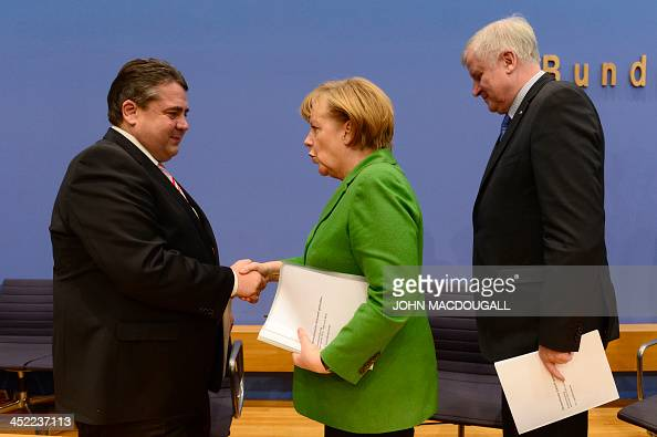 Head of Social Democratic Party Sigmar Gabriel shakes hands with German Chancellor and head of Christian Democratic Party Angela Merkel next to...
