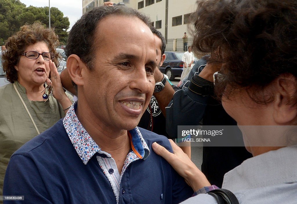 Head of the Arabic version of independent news website Lakome Ali Anouzla (C-L), smiles as he is greeted by members of his support committee after his was freed on bail on October 25, 2013 in the Moroccan city of Rabat. The Moroccan journalist was arrested on September 17, 2013 after his website posted a link to a video attributed to Al-Qaeda in the Islamic Maghreb (AQIM), with the authorities saying he was giving the jihadists a platform.