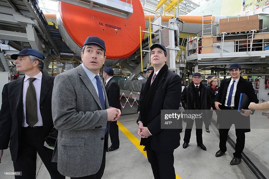 Head of the assembly line at Airbus A380 assembly plant Thierry Bayol (2ndL) and French minister for Industrial renewal Arnaud Montebourg (C) visit the plant on January 25, 2013 in Colomiers.