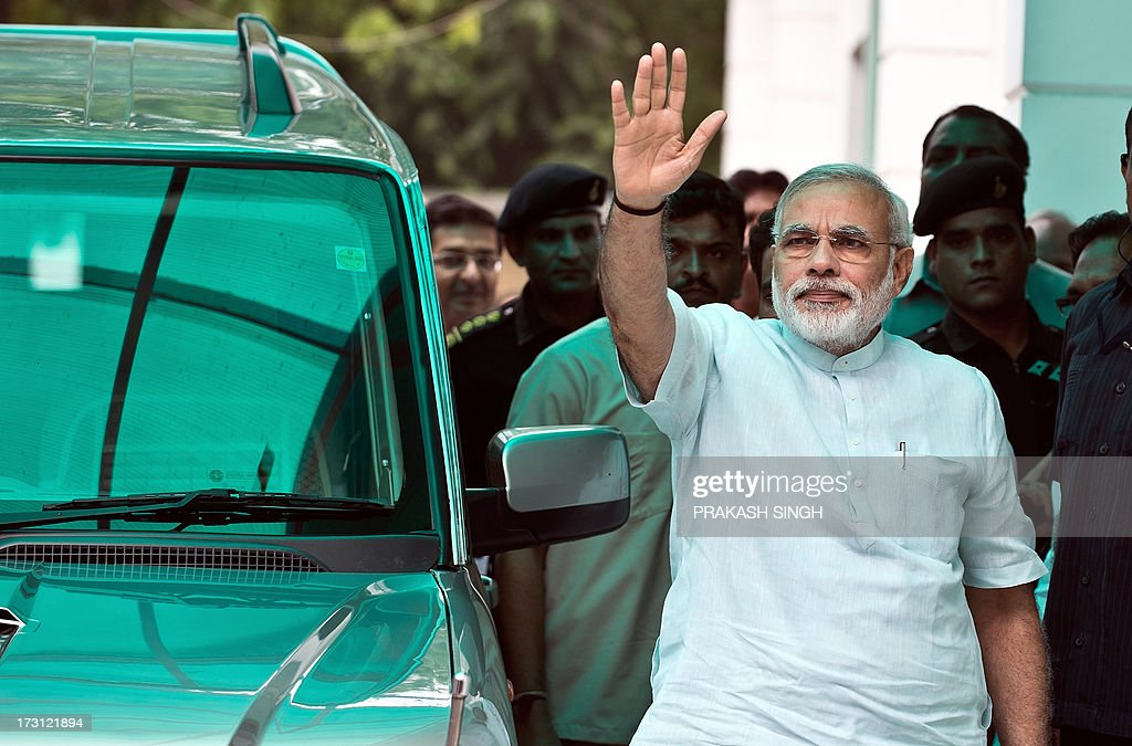 Head of the Bharatiya Janata Party (BJP) poll panel and Gujarat chief minister Narendra Modi waves on his arrival at party headquarters for the BJP's Parliamentary Board meeting in New Delhi on July 8, 2013. Modi attended the second meeting of the Parliamentary Board as the party gears up for 2014 Lok Sabha elections with the Parliamentary Board likely to finalise Modi's blueprint for the 2014 polls. AFP PHOTO/ Prakash SINGH