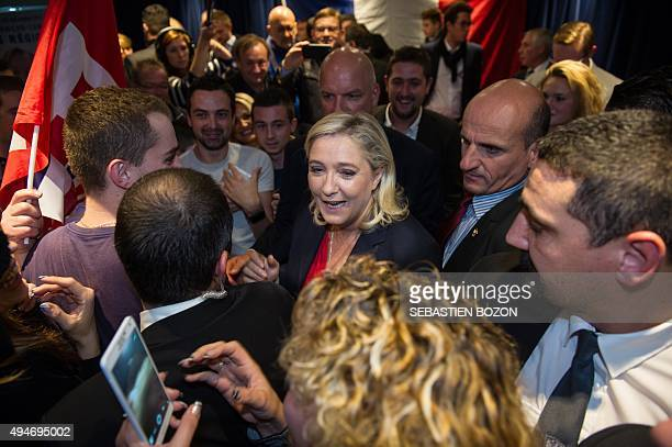Head of the Front National farright party Marine Le Pen greets supporter on October 28 in Besancon after attending an election campaign for FN top...