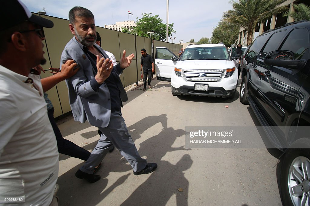 Head of the Iraqi Fadhila Party Ammar Tohme is escorted to his car by a protester (L) who tries to protect him as thousands broke into the parliament in Baghdad's heavily fortified 'Green Zone' on April 30, 2016. Thousands of angry protesters broke into Baghdad's Green Zone and stormed the parliament building after lawmakers again failed to approve new ministers. Jubilant supporters of cleric Moqtada al-Sadr invaded the main session hall, shouting slogans glorifying their leader and claiming that they had rooted out corruption. / AFP / HAIDAR