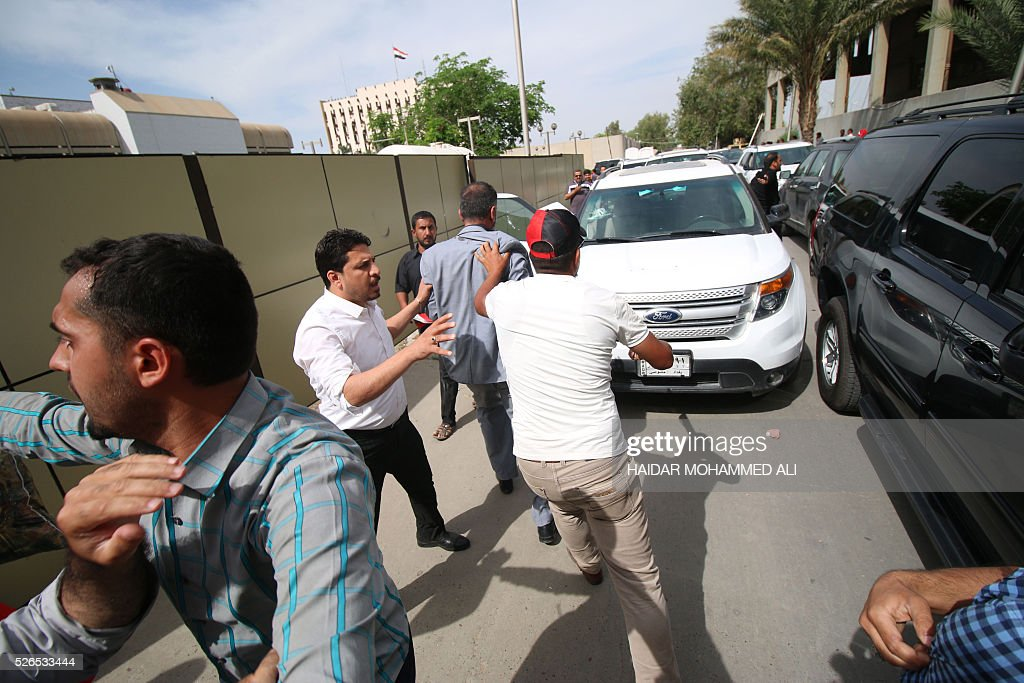 Head of the Iraqi Fadhila Party Ammar Tohme (C-L) is escorted to his car by a protester (C-R) who tries to protect him as thousands broke into the parliament in Baghdad's heavily fortified 'Green Zone' on April 30, 2016. Thousands of angry protesters broke into Baghdad's Green Zone and stormed the parliament building after lawmakers again failed to approve new ministers. Jubilant supporters of cleric Moqtada al-Sadr invaded the main session hall, shouting slogans glorifying their leader and claiming that they had rooted out corruption. / AFP / HAIDAR