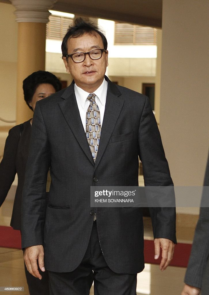 Head of the opposition Cambodia National Rescue Party Sam Rainsy walks at the National Assembly building in Phnom Penh on December 19 2014 Cambodian...