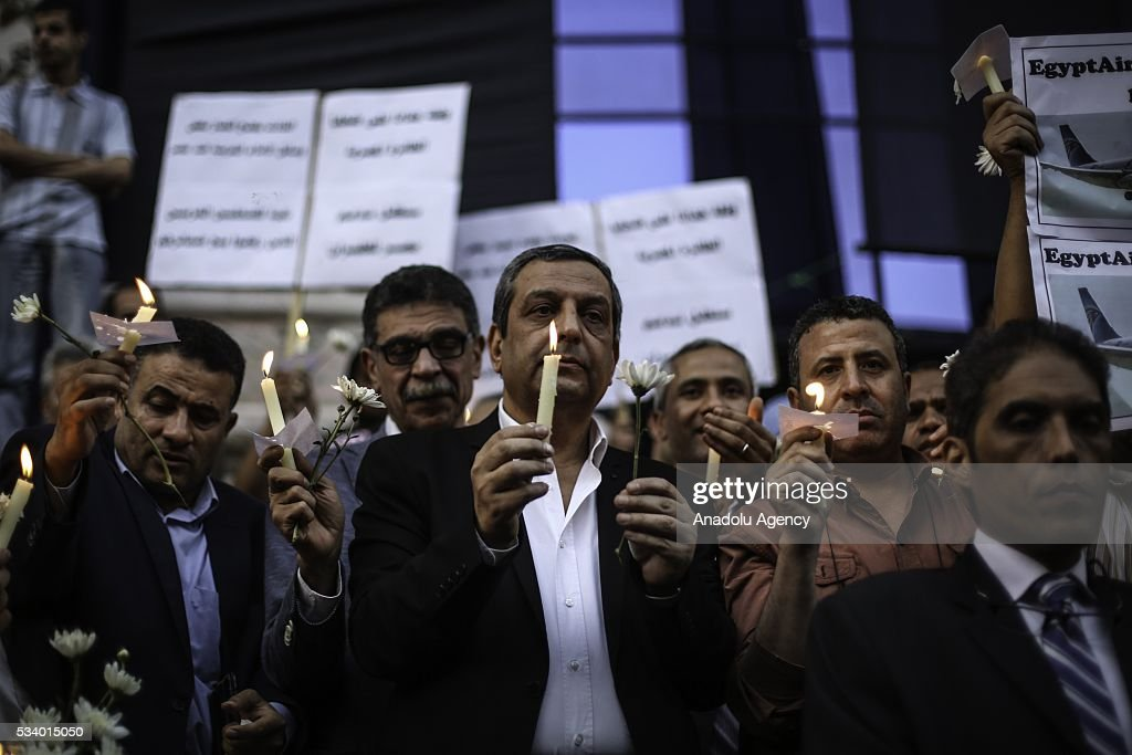 Head of the Syndicate of Journalists Yahya Kallas (C) lights a candle during a commemoration ceremony for the 66 victims of EgyptAir flight MS804 crash in front of the association of journalists building in Cairo, Egypt on May 24, 2016.