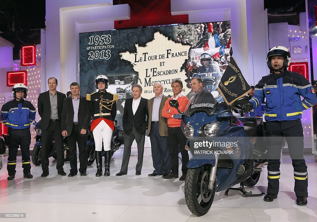 Head of the Tour de France cycling race Christian Prudhomme (2ndL) former Tour de France winner Bernard Thevenet (3rdL), TV host Michel Drucker (C), journalists Jean-Paul Ollivier (4thR) and Gerard Holtz (3rdR) and former Tour de France winner Bernard Hinault (2ndR) pose with pilots of motocyclists squadron of the Republican guard, on February 20, 2013 in Paris, as part of the celebrations of the squadron's 60th anniversary.