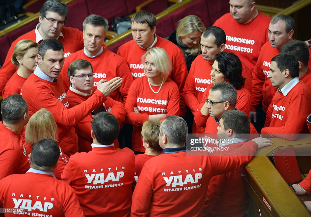"""Head of Ukrainian opposition party UDAR ( Punch) and boxing heavy-weight World champion Vitaliy Klitschko (2L) speaks to deputies of the party wearing t-shirts signed 'Vote personally"""" as they block the parliamentary tribune to prevent the opening of the session in Kiev on February 19, 2013. The dispute in Ukraine's one-chamber parliament, known as the Verkhovna Rada, centres on opposition demands for each deputy to vote individually. Voting in the Ukrainian legislature is done electronically and lawmakers can delegate the right to vote to their colleagues."""