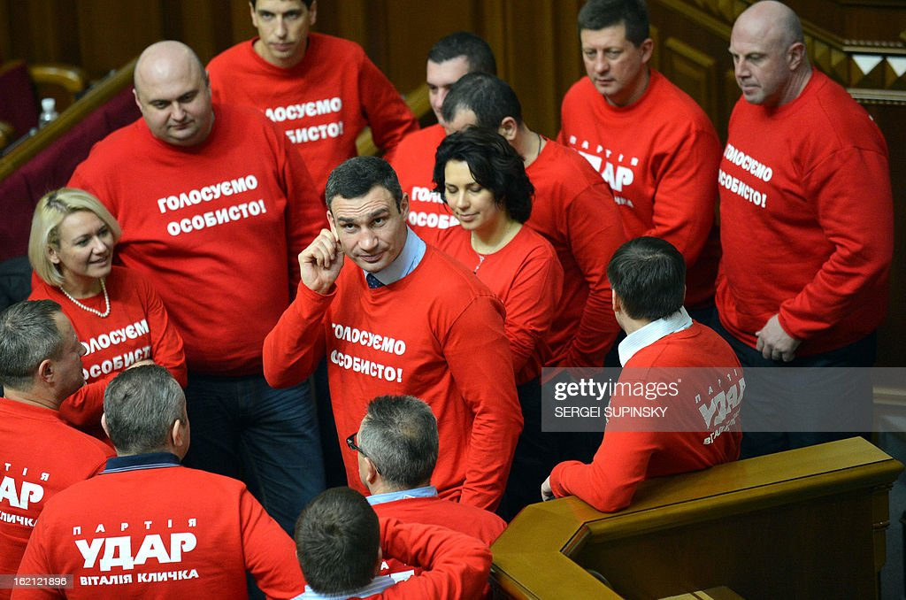 """Head of Ukrainian opposition party UDAR ( Punch) and boxing heavy-weight World champion Vitaliy Klitschko (C) gestures as he speaks to deputies of the party wearing t-shirts signed 'Vote personally"""" as they block the parliamentary tribune to prevent the opening of the session in Kiev on February 19, 2013. The dispute in Ukraine's one-chamber parliament, known as the Verkhovna Rada, centres on opposition demands for each deputy to vote individually. Voting in the Ukrainian legislature is done electronically and lawmakers can delegate the right to vote to their colleagues."""