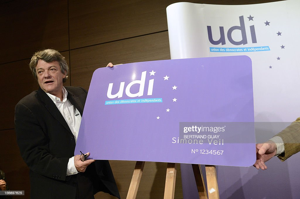 Head of Union of Democrats and Independents (UDI) party, Jean-Louis Borloo poses with a pannel representing the first UDI membership card during a meeting with new UDI members on November 24, 2012 at the 'Maison de la Mutualite' conference centre in Paris. France's centre-right UDI and far-right Front National (FN) recently declared registering an increasing number of new memberships since the bitterly contested leadership election of main opposition right-wing party Union for a Popular Movement (UMP).