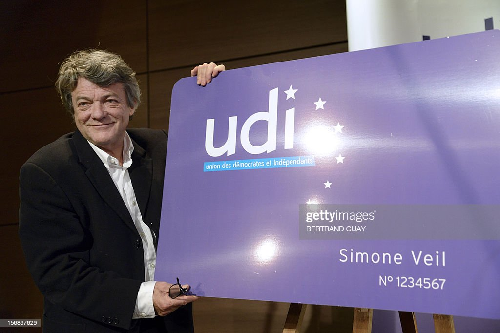 Head of Union of Democrats and Independents (UDI) party, Jean-Louis Borloo poses with a pannel representing the first UDI membership card during a meeting with new UDI members on November 24, 2012 at the 'Maison de la Mutualite' conference centre in Paris. France's centre-right UDI and far-right Front National (FN) recently declared registering an increasing number of new memberships since the bitterly contested leadership election of main opposition right-wing party Union for a Popular Movement (UMP). AFP PHOTO BERTRAND GUAY