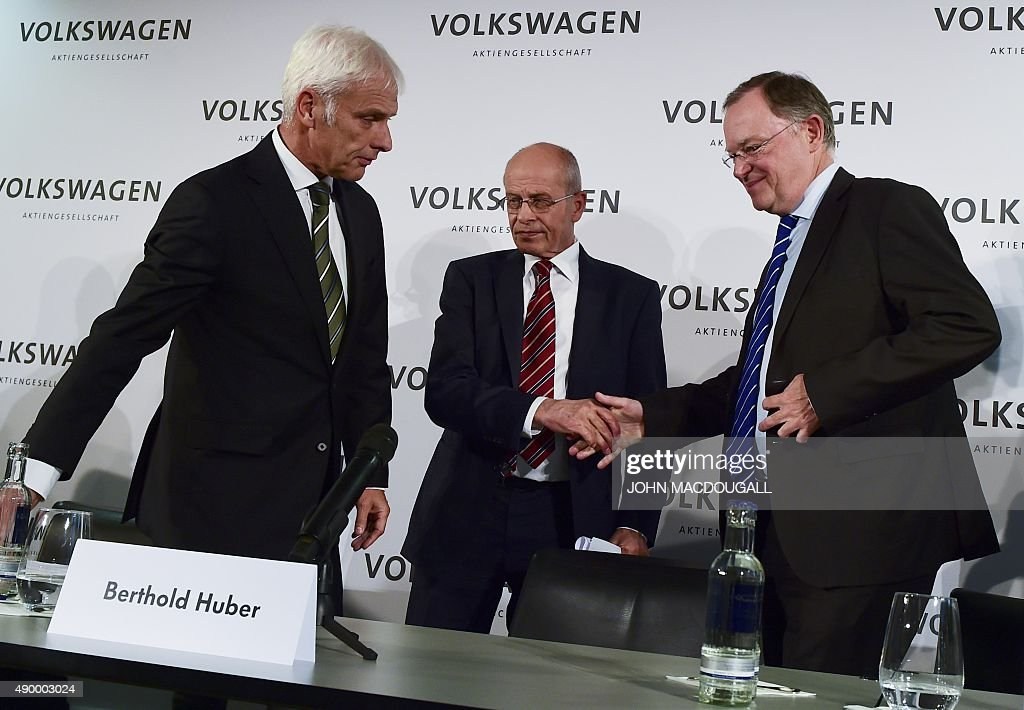 Head of Volkswagen's (VW) Supervisory board <a gi-track='captionPersonalityLinkClicked' href=/galleries/search?phrase=Berthold+Huber&family=editorial&specificpeople=2087477 ng-click='$event.stopPropagation()'>Berthold Huber</a> (C) shakes hands with Supervisory board member <a gi-track='captionPersonalityLinkClicked' href=/galleries/search?phrase=Stephan+Weil&family=editorial&specificpeople=4683319 ng-click='$event.stopPropagation()'>Stephan Weil</a> next to Matthias Mueller (L), newly appointed CEO of German car maker Volkswagen at the company's the headquarters in Wolfsburg, central Germany, on September 25, 2015 after the company's supervisory board meeting. Matthias Mueller, previously head of luxury sportscar maker Porsche, takes the steering wheel at scandal-hit Volkswagen, replacing Martin Winterkorn who quit over the global pollution cheating scandal engulfing the group. AFP PHOTO / JOHN MACDOUGALL