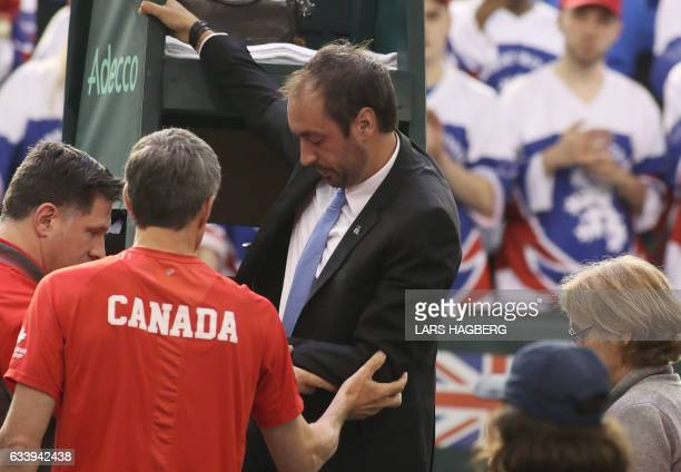 Head referee Arnaud Gabas from France is helped down from the his chair after Denis Shapovalov of Canada accidently hit him with a tennis ball during...