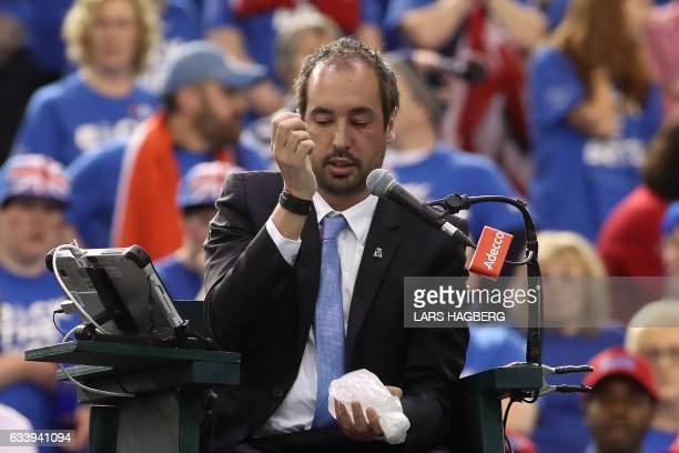 Head referee Arnaud Gabas sits with an ice pack on his eye after Denis Shapovalov of Canada accidently hit him with a tennis ball during the third...