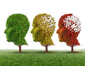 Memory loss and brain aging due to dementia and alzheimer's disease as a medical icon of a group of color changing autumn fall trees shaped as a human head losing leaves as intelligence function on a