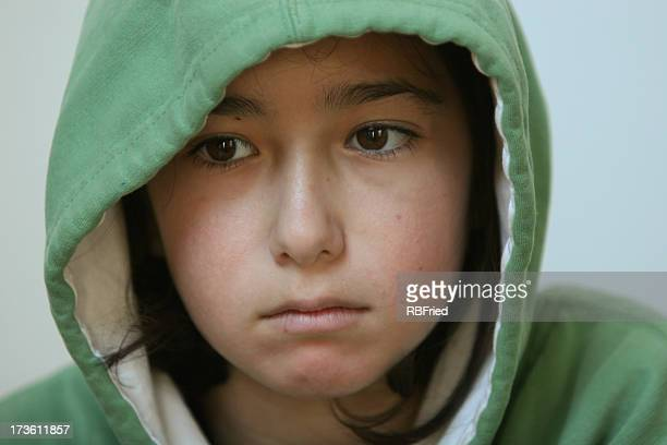 Head shot of a child in a green hoodie looking sad