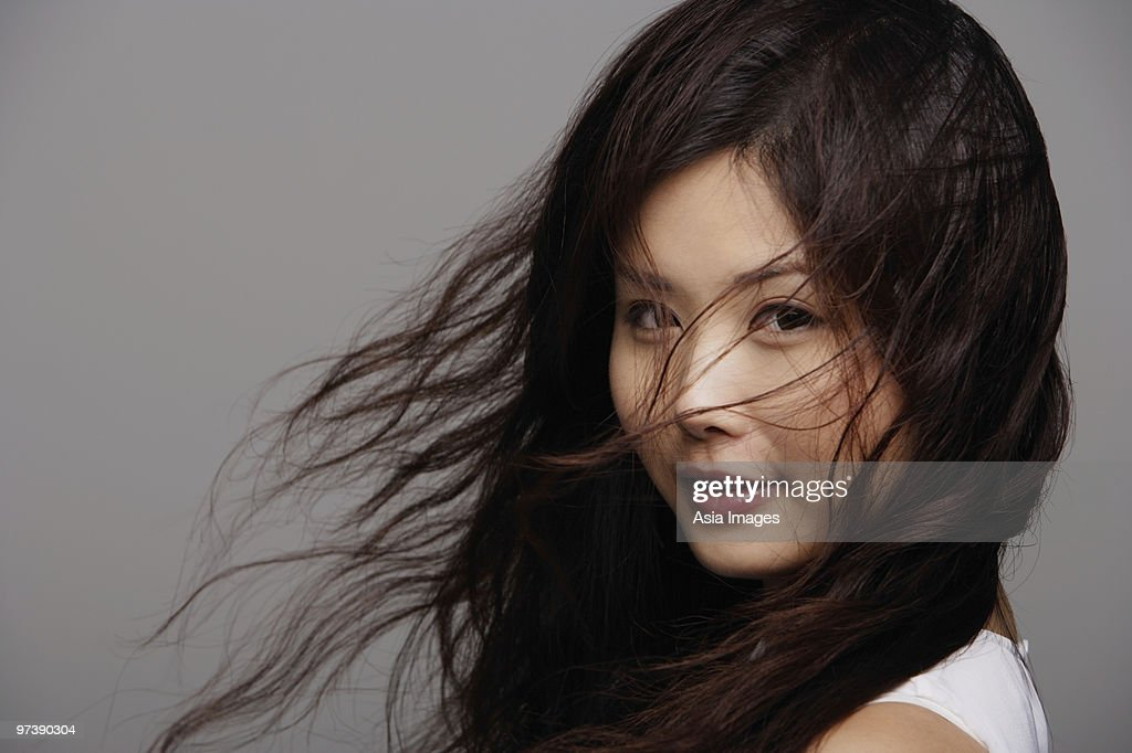 Head shot of Chinese woman with wind blown hair : Stock Photo