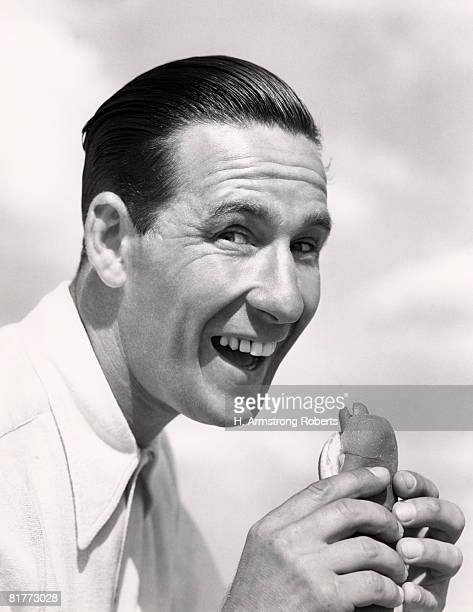 Head Shot Of Smiling Man With Wide Open Mouth And Head Pushed Forward About To Eat A Hotdog In A Frankfurter Roll Wearing A White Shirt Buck Teeth Hair.