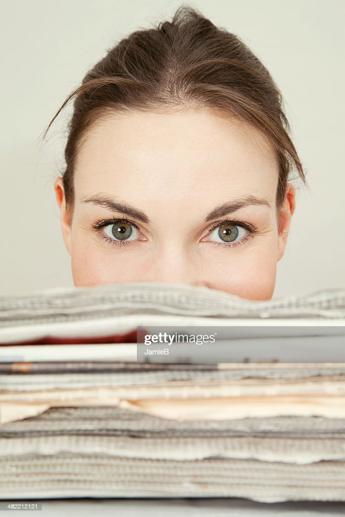 Head shot of young woman looking over the top of a stack of newspapers