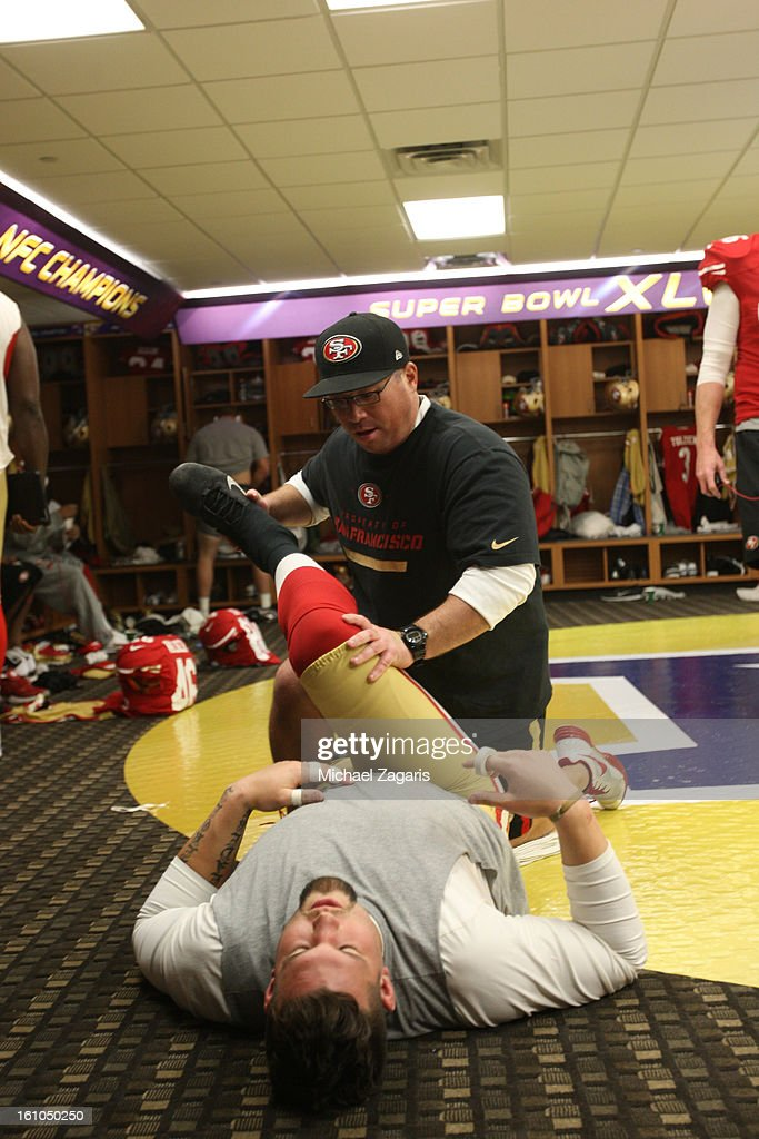 Head Strength and Conditioning Coach Mark Uyeyama of the San Francisco 49ers sretches Alex Boone #75 in the locker room prior to Super Bowl XLVII against the Baltimore Ravens at the Mercedes-Benz Superdome on February 3, 2013 in New Orleans, Louisiana. The Ravens won 34-31.