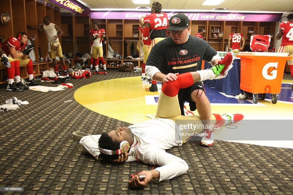 Head Strength and Conditioning Coach Mark Uyeyama of the San Francisco 49ers stretches Michael Crabtree #15 in the locker room prior to Super Bowl XLVII against the Baltimore Ravens at the Mercedes-Benz Superdome on February 3, 2013 in New Orleans, Louisiana. The Ravens won 34-31.